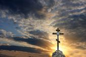 Cross on dramatic sky sunset background