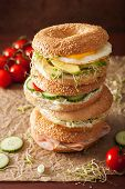 variety of sandwiches on bagels: egg, avocado, ham, tomato, soft cheese, alfalfa sprouts poster
