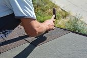 Roofer Installing Asphalt Shingles On House Roofing Construction Roof Corner With Hammer And Nails.  poster