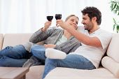 Young couple having a glass of wine in their living room