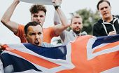 Group of angry men showing a UK flag and blank boards shouting during a protest poster
