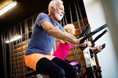 Mature Fit People Biking In The Gym, Exercising Legs Doing Cardio Workout Cycling Bikes poster