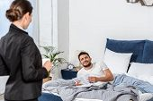 Girlfriend Holding Cup Of Coffee In Suit And Boyfriend In Pajamas Reading Newspaper In Bedroom In Mo poster