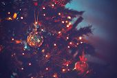 Beautiful Christmas tree in dark evening light with festive xmas lights on it, cozy family holiday a poster