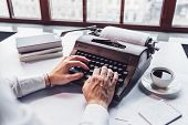 Young writer typing on a retro typewriter close-up poster
