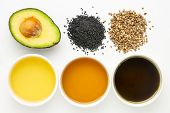 health oils from avocado, black seed and hemp seeds - top view of ceramic bowls with corresponding s poster