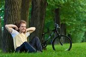 Cyclist Young Man With Fury Hair Sitting By A Tree In A Park On The Grass Meditating, His Bicycle Be poster