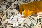 Medication from a pill bottle spilled on cash.  Use for any type of medical, insurance or financial
