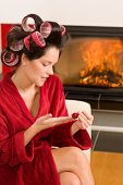 Home beauty woman with curlers checking manicure nail polish fireplace