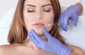 The Doctor Cosmetologist Makes Lip Augmentation Procedure Of A Beautiful Woman In A Beauty Salon.cos poster