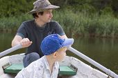 father with son in row boat - summertime