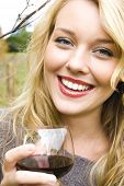 Beautiful young woman in a vineyard drinking wine