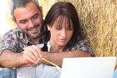 Farming couple sat with laptop computer