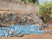 A river in Ethiopia is clogged with empty plastic bottles, environmental disaster. poster