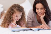 Little girl reading bedtime story with her young mother