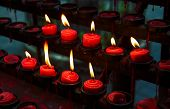 Red Candles With Yellow Flame On Catholic Church Altar. Burning Candle Closeup Photo. In Memoriam Ba poster