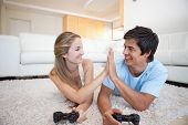 stock photo of video game controller  - Playful cute couple playing video games in their living room - JPG