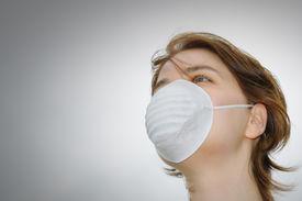 foto of avian flu  - Woman wears protective mask against flu or pollution - JPG