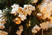 Traditional handcrafted popcorn garland (strung together with golden jingle bells) on artificial chr