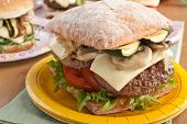 Delicious cheeseburger with mushrooms and zucchini on ciabatta bread