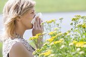 picture of blowing nose  - Side view of woman blowing nose into tissue in front of flowers - JPG