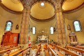 Bancas y altar entre columnas de la iglesia católica de Madonna Moretta en Alba, Italia.