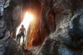 stock photo of cave  - Young explorer standing in a cave with climbing equipment ready for action - JPG