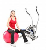 Young female resting on a pilates ball next to a cross trainer isolated on white background