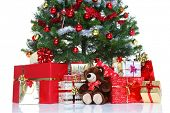 Decorated Christmas tree with baubles and tinsel surrounded by gift wrapped presents and a teddy bea