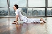 Side view of a young man doing Upward Facing Dog pose at gym