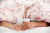 Romantisches paar Hand in Hand unter der Bettdecke im Bett