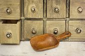 empty rustic wooden scoop with a primitive apothecary drawing cabinet in a background