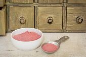 yumberry fruit powder - bowl and measuring tablespoon  with a primitive apothecary drawer cabinet in background