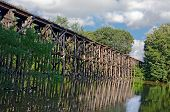 picture of trestle bridge  - Old wooden train trestle over a river with water reflection - JPG