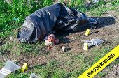stock photo of morbid  - Crime scene with male corpse and evidence markers - JPG