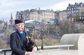 EDINBURGH, SCOTLAND, UNITED KINGDOM - APRIL 10 : Unidentified Scottish Bagpiper playing music with b