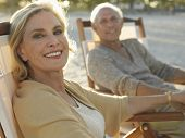 stock photo of retirement age  - Portrait of happy middle age woman with man relaxing on deckchairs at beach - JPG