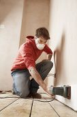 Full length of man wearing mask while sanding wall in unrenovated room