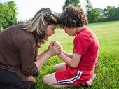 stock photo of adoration  - Single mother and child in humble communication through prayer with his Creator in heaven - JPG