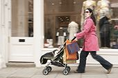 stock photo of overcoats  - Full length side view of young mother pushing baby stroller by clothes shop - JPG