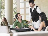 image of waiter  - Waiter serving wine to young couple at outdoor restaurant - JPG