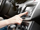 stock photo of driver  - finger on dashboard with gps panel and tv - JPG