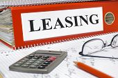stock photo of rental agreement  - leasing contracts in folder with calculator and red pencil - JPG