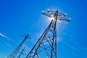 a power mast of a high voltage transmission line against blue sky with sun
