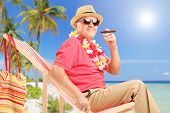 Gentleman smoking a cigar and enjoying on a sun lounger on a tropical beach next to a sea and palm t