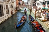 Italy, Venice - July 2012: Gondolas With Tourists Cruising A Small Venetian Canal On July 16, 2012 I