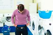 Young man in a launderette, washing his dirty laundry, in the background are washing machines, he is