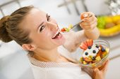 stock photo of anonymous  - Happy young housewife eating fruits salad  - JPG