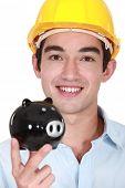 Builder holding piggy-bank