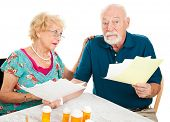 Senior couple going over their medical bills.  They are confused and overwhelmed.  White background.